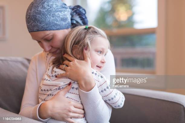 young ethnic mom with cancer holds her daughter tightly - resilience stock photos and pictures