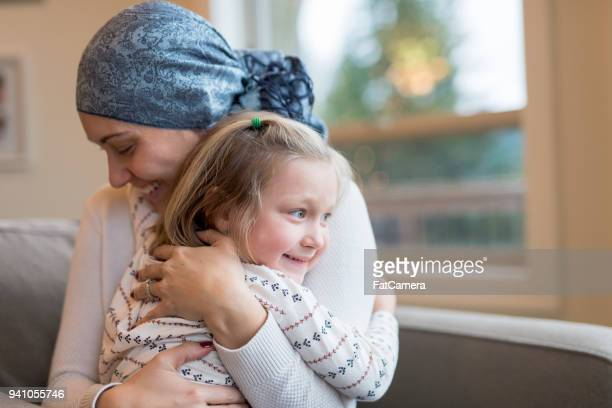 young ethnic mom with cancer holds her daughter tightly - cancer stock photos and pictures