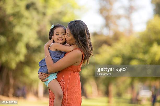 Young ethnic mother embracing her toddler girl outdoors