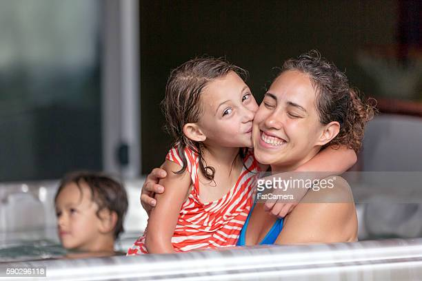 Young ethnic mother posing with her daughter in a hot tub