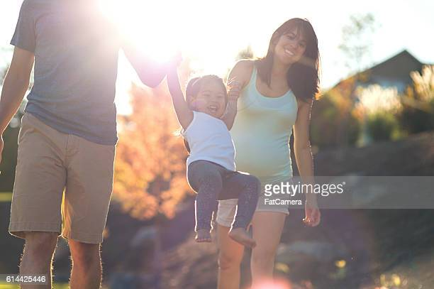 Young ethnic parents swinging their daughter by her hands