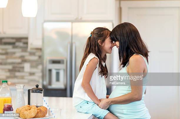 Young ethnic pregnant mother sharing a moment with her daughter