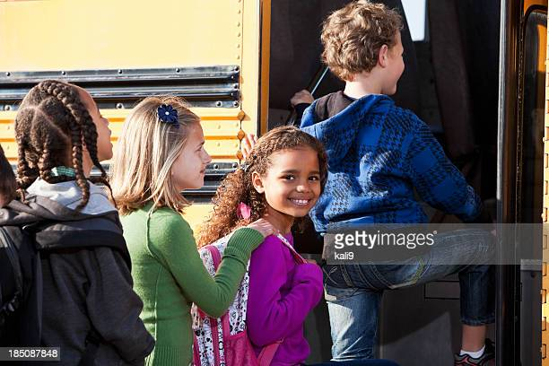 Young ethnically diverse students boarding bus