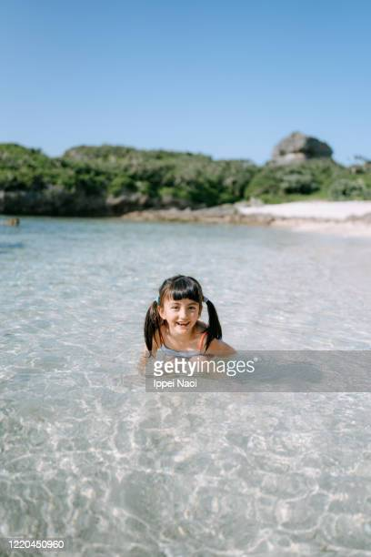 young eurasian girl playing in tropical beach water, okinawa, japan - ippei naoi stock pictures, royalty-free photos & images