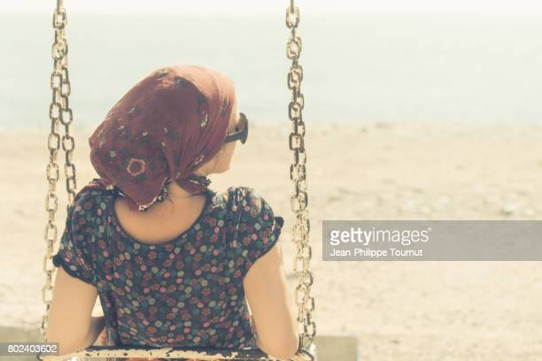 young european woman sitting on a swing on a beach near bandar lengeh, a harbour of the persian gulf, hormozgan province, southern iran - cross processed stock pictures, royalty-free photos & images
