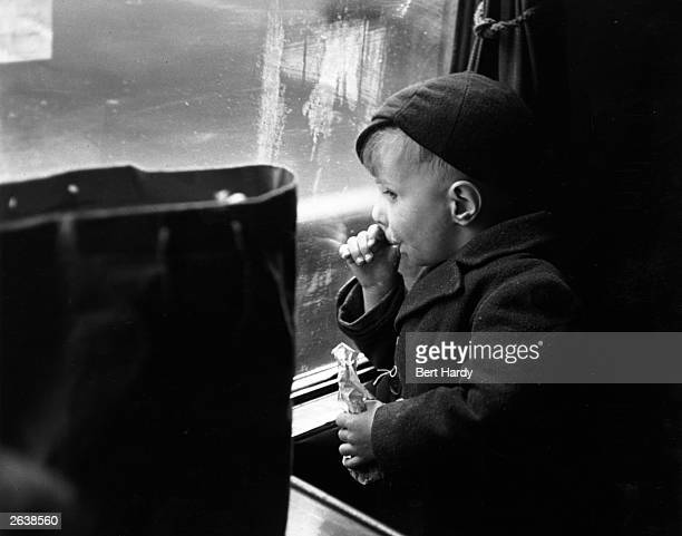 A young evacuee on a train sucking his thumb as he watches the view from the window Original Publication Picture Post 1133 Wartime Terminus pub 1942