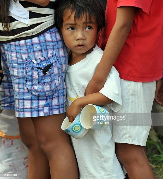 A young evacuee queues up for free ice cream at an evacuation center in Legazpi City Albay province southeast of Manila on December 23 2009 With tens...