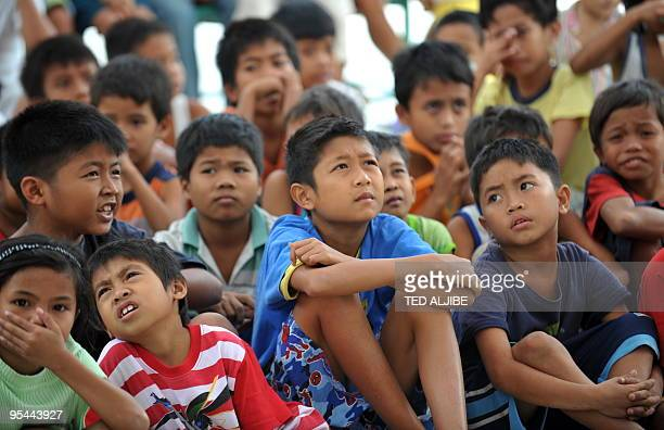 Young evacuees affected by the rumbling Mayon volcano watch television at a temporary shelter in the town of Guinobatan in Albay province on December...