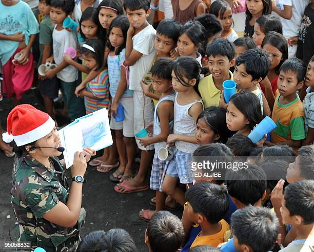 Young evacuees listen to a military personnel during a readalong activity as they queue up for free ice cream at an evacuation center in Legazpi City...