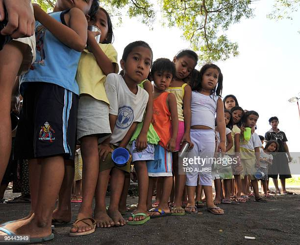 Young evacuees queue up for free ice cream at an evacuation center in Legazpi City Albay province southeast of Manila on December 23 2009 With tens...