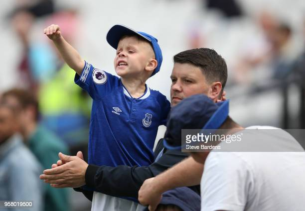 A young Everton fan cheers on his team prior to the Premier League match between West Ham United and Everton at London Stadium on May 13 2018 in...
