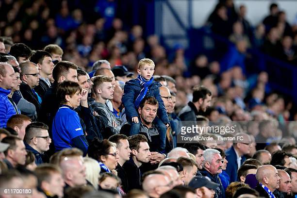 A young Everton fan sits upon his dads shoulders during the Barclays Premier League match between Everton and Crystal Palace at Goodison Park on...