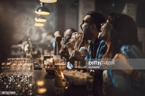joven había excitado los fanáticos divirtiéndose en un bar mientras animando a su equipo favorito. - partido rondas deportivas fotografías e imágenes de stock