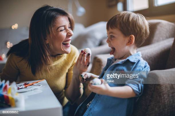 young excited woman giving her little son easter egg - happy easter mom stock pictures, royalty-free photos & images