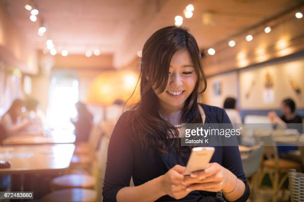 young executive director typing message during business meeting in cafe - one mid adult woman only stock pictures, royalty-free photos & images