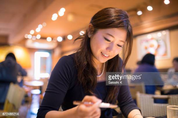 Young executive director writing document in meeting at cafe