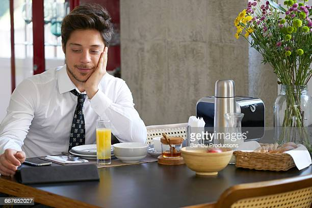 Young executive man having breakfast and  working