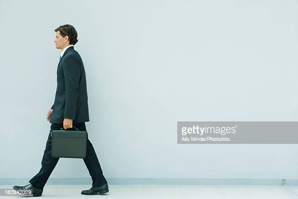 Young executive walking with briefcase, side view