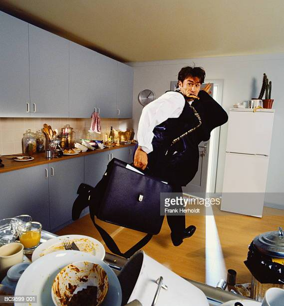 Young executive with slice of toast in mouth, rushing from kitchen