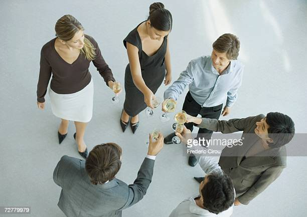 Young executives raising glasses for toast, high angle view