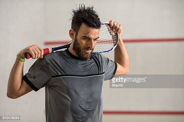 young exhausted squash player with a racket. - squash sport stock pictures, royalty-free photos & images