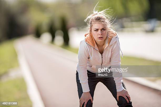 Young exhausted woman taking a breath after jogging.