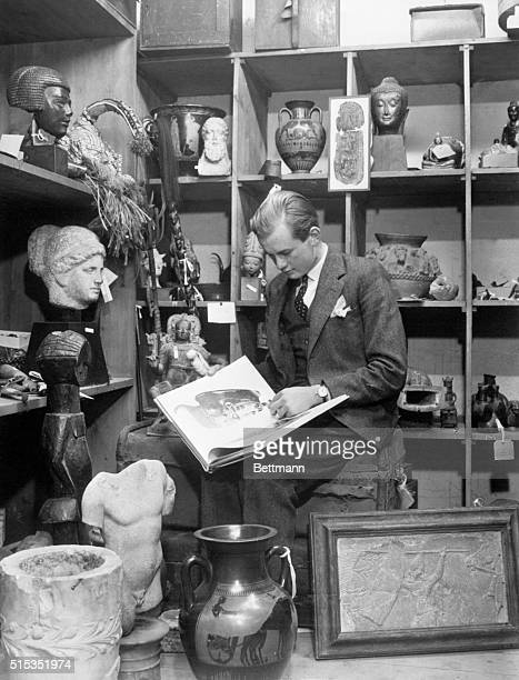 Young expert on things old, Bruce Chatwin examines some antiques in Sotheby's upstairs warehouse. Behind him, art works from different cultures and...