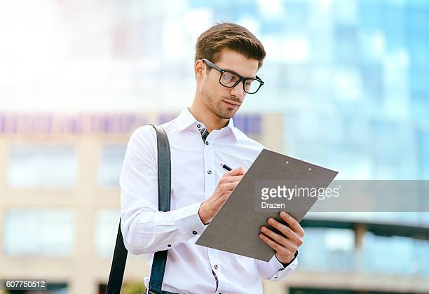 young expert signing the document near office building - surveyor stock photos and pictures