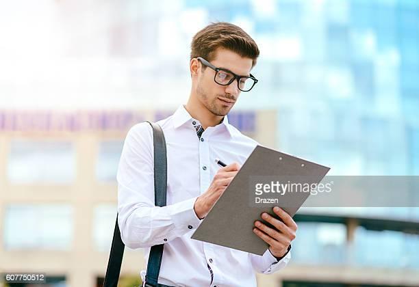 young expert signing the document near office building - inspetora - fotografias e filmes do acervo