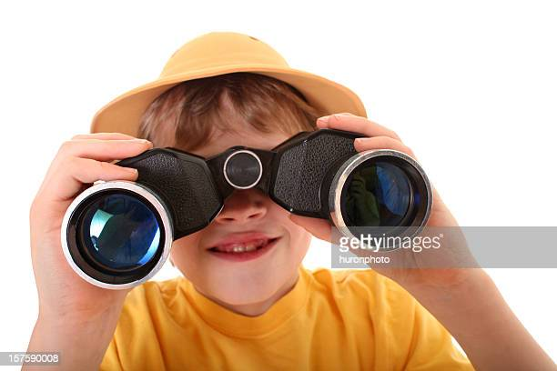 Young explorer boy using binoculars