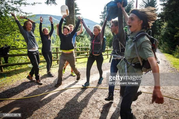 young explorers jump for joy at end of race - grupo de competencia fotografías e imágenes de stock