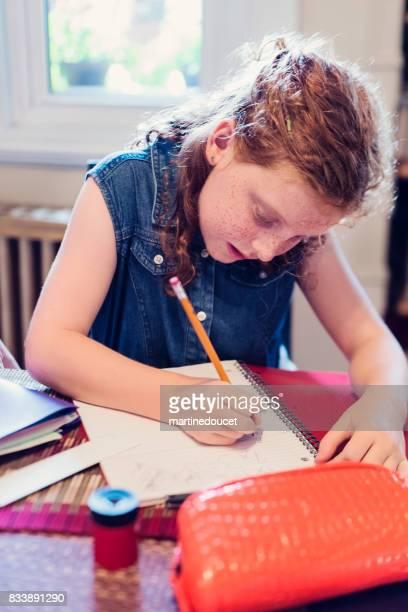 """jovem expressiva ruiva fazendo lição de casa escola em casa. - """"martine doucet"""" or martinedoucet - fotografias e filmes do acervo"""