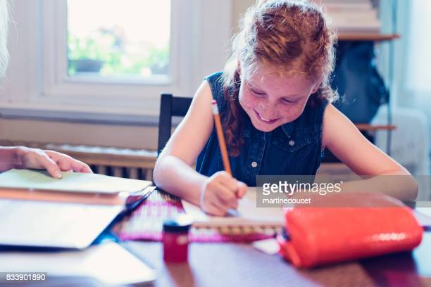 "chica joven pelirroja expresiva haciendo tareas escolares en casa. - ""martine doucet"" or martinedoucet fotografías e imágenes de stock"