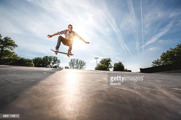 young extreme skateboarder practicing at the park. - ollie pictures stock pictures, royalty-free photos & images
