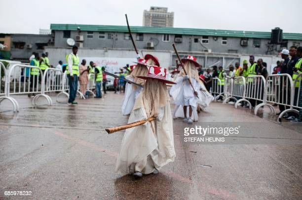 A young Eyo masquerader dances as he leads the group into the Tafawa Balewa Square in Lagos on May 20 2017 The whiteclad Eyo masquerades represent...