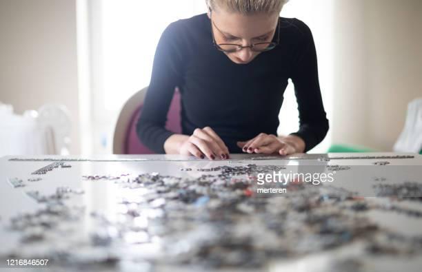 giovane famale che gioca puzzle in quarantena - puzzle foto e immagini stock