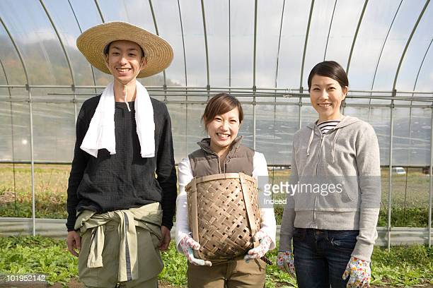 Young famers smiling in plastic greenhouse
