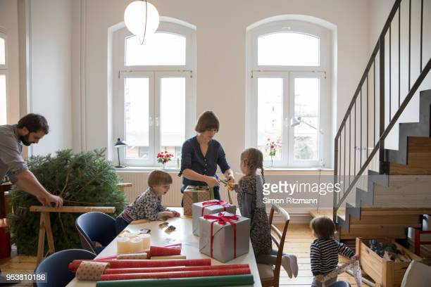 young familiy wrapping christmas presents and preparing christmas tree in living room - avvolto foto e immagini stock