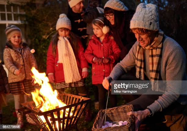 Young family and friends around fire