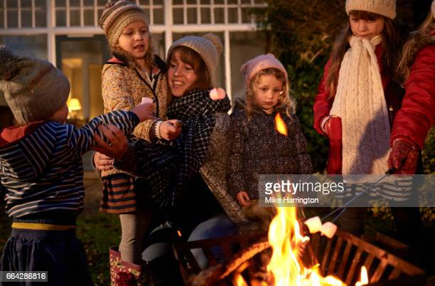 Young family and friends enjoying cold winters night