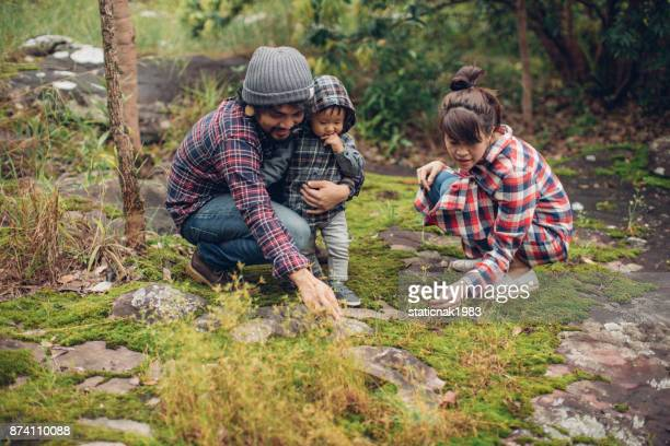 Young family and son sitting on rock in forest at Thailand.