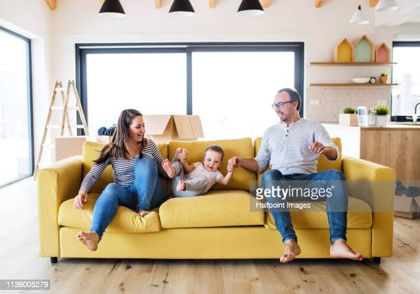 young family and toddler boy with boxes moving in a new home, having fun on a sofa. - small apartment stock pictures, royalty-free photos & images