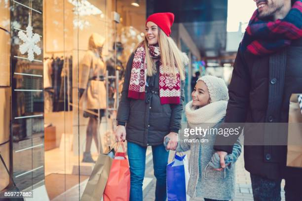 young family at christmas shopping - holiday shopping stock photos and pictures