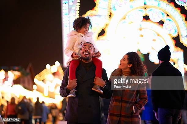Young family at funfair, father carrying daughter on shoulders