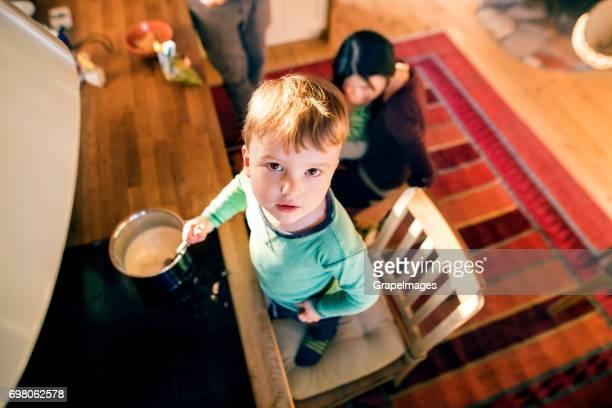 Junge Familie zu Hause. Kleiner Junge Kochen Brei auf Herd, mischen.