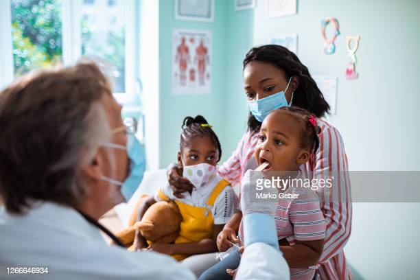 young family at the pediatrician - healthcare stock pictures, royalty-free photos & images