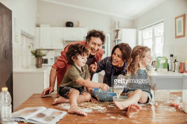 young family baking together - young family stock pictures, royalty-free photos & images