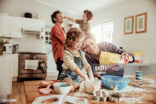 young family baking together - kitchen stock pictures, royalty-free photos & images