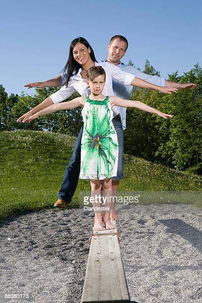 Parents with daughter balancing on plank in playground, portrait