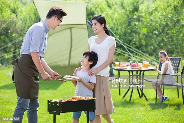 young family barbecuing outdoors - girls with short skirts - fotografias e filmes do acervo